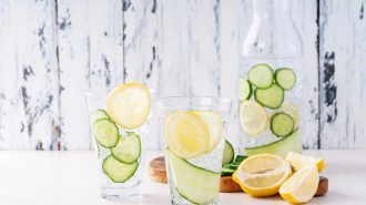Cucumber and lemon infused water in glasses and bottle served with ice over bright white wooden background.